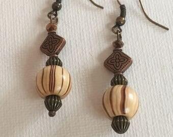 Copper dangle earrings.  Copper drop earrings.  Copper brown and cream dangle earrings hanging on copper ear wires. Copper embellishment.
