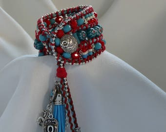 Tasseled wrap bracelet in red, white and blue . Cowboy hat,horse and concho charms. Red and blue leather braided cord with glass beads