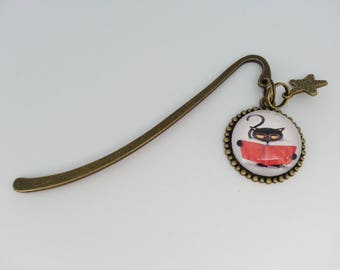 Bookmark with a round glass cabochon. CAT and red and white polka dots.