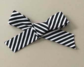 Black and white stripped fabric bow on one size fits most nylon headband OR alligator clip
