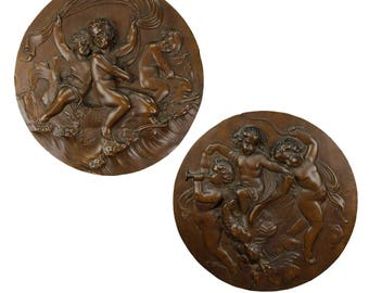 a pair of elaborate carved nutwood plaques with putti, ca. 1900