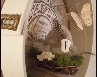 Easter egg in his basket, feathers, old fabric flowers.
