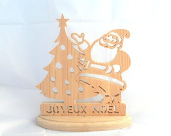 Carved wooden Santa Claus and Christmas tree Christmas decoration Merry Christmas.