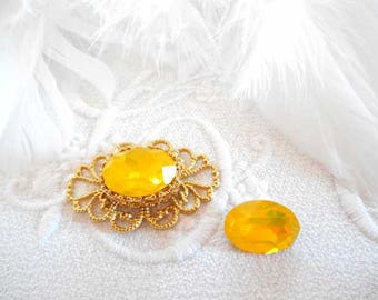 A cabochon 10 x 14 mm oval yellow crystal.