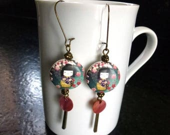 Earrings made of porcelain beads with pink sequins of mother-of-Pearl and metal charms kokeshi style doll pattern