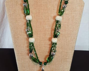 Necklace made of green and off-white beads with horn-shaped pendant