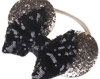 Children's gold Minnie Mouse elastic headband with a black sparkling bow.