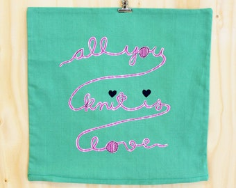 all you knit is love - pin and green appliquéd cushion cover