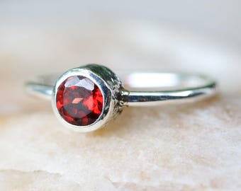 Round faceted garnet ring in silver bezel setting with sterling silver high polish finished band