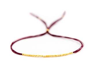 Gold beads on deep red silk