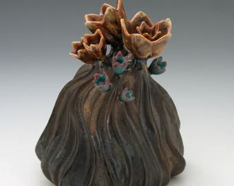 Carved porcelain sculpture with flowers in bronze, gold and turquoise