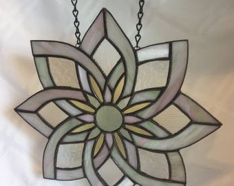 A floral stained glass window panel in soft pinks, greens, creams and greys