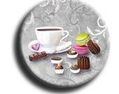 Aimant, Magnet rond de gourmandises avec 3 macarons, des chocolats, un canelé et une tasse sur fond gris avec
