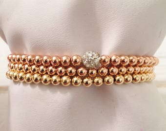 Set of three 14k rose gold and gold filled beads; stretch bracelets