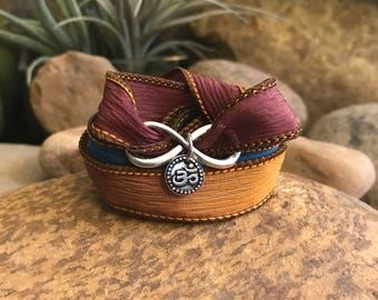 Om infinity earthy wrap bracelet with silk ribbon and charms. Great gift for yogi enthusiasts or yoga teacher