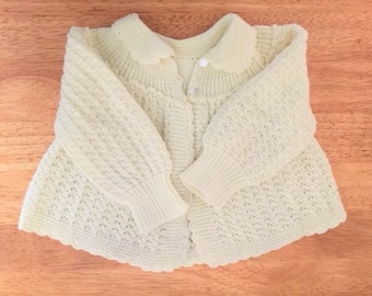 BABY SWEATER for infant 3 - 6 months and hand-knit in pale yellow with 2 pearl buttons in front and scalloped edges on collar and bottom.
