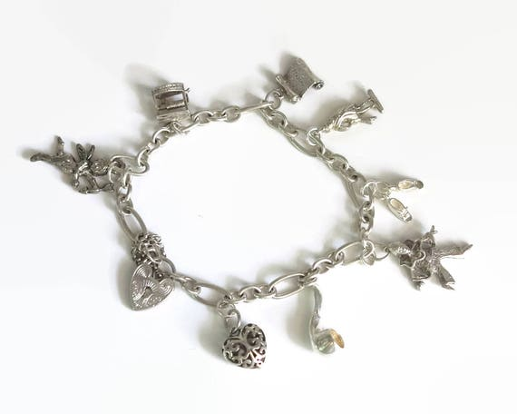 Sterling silver bracelet with 8 different sterling silver charms, padlock closure, safety chain, fancy links, 8 inches / 20.5 cm, 21 grams