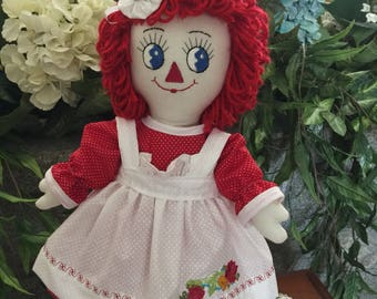 Raggedy Ann doll in red and white with red roses embroidered on the apron .