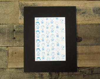 TWO Vintage Peanuts prints - featuring Charlie Brown, Snoopy and Gang. Both prints are pattern-like, with blue illustrations of characters.