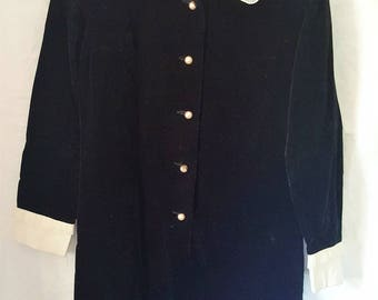 1960's black velvet tunic dress with cream cuffs & collar with decorative pleats. Pearl style round buttons. Suit size 10. Vintage clothing.
