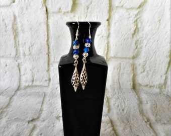 Intricate sterling silver teardrop earrings with electric blue glass beads.