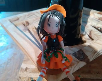Decorative figurine: Maeva little witch and her pumpkin in cold porcelain.