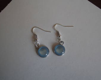 Dangling earrings in silver and light blue glass cabochon