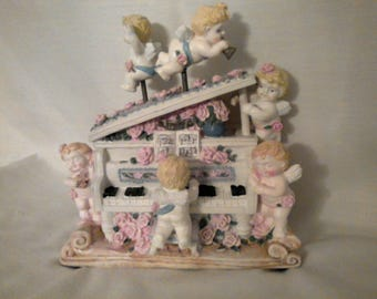 """Vintage Cherubs Playing The Piano. 7"""" long, 7"""" high, 5 1/2"""" deep. made of resin."""