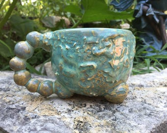 glossy turquoise blue tripod mug with textured structure motif