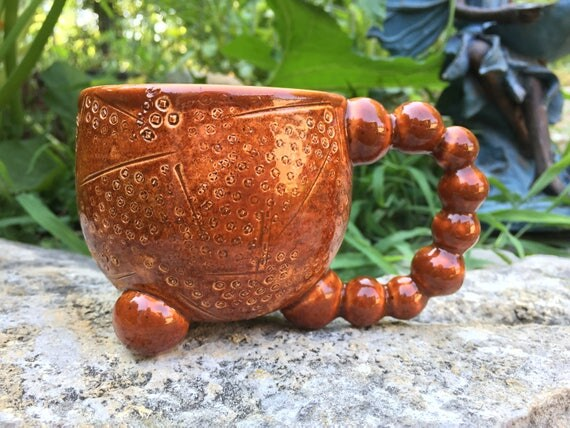 glossy sienna brown tripod mug with textured structure motif