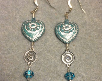 Opaque turquoise with silver inlay Czech glass heart bead dangle earrings adorned with silver swirly links and turquoise Saturn beads.