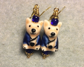 Tan and blue ceramic puppy dog dangle earrings adorned with dark blue Czech glass beads.
