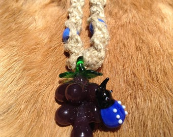 Bundle of grapes with blue lady bug glass pendant on natural hemp necklace with beads