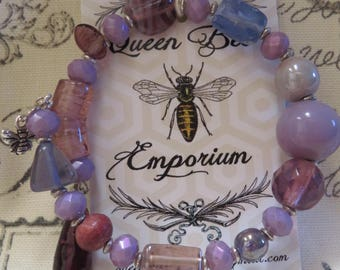 Shades of chunky purple glass beads accented with silver and a bee charm on a memory wire bracelet