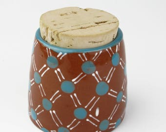 Small Ceramic jar ,with corked lid and turquoise and white polka dot pattern.
