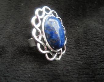 the contours of interlaced silver metal and gemstone ring