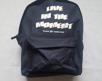 """Navy blue Backpack. """"Live in the moment"""". Also check houseofaudacious.com for more items."""