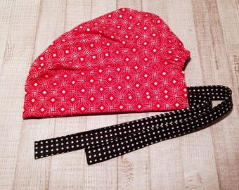 Red geomtric pattern with black and white polka dot tie.