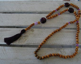 Long necklace of honey-colored wooden beads, lampwork glass and purple crackled glass beads and matching pompon tassel