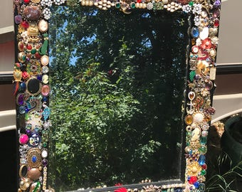 Mirror with jeweled embellished frame.
