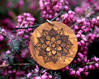Pendant with laser-engraved mandala flower made of olive wood on a leather belt