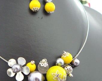mustard yellow dress and grey made of metal, ceramic, glass beads.