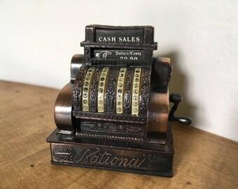 Die cast cash register pencil sharpener.
