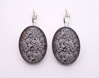Oval earrings decorated with fine white flowers on a black background