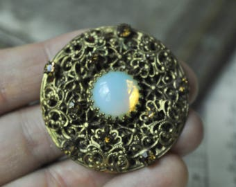 Vintage filigree brass brooch with glass rhinestones.