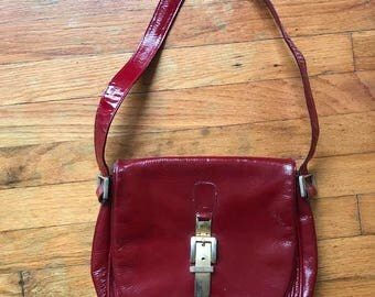 Red patent leather vintage handbag with brass buckle