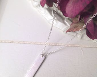 Sterling silver drop bar necklace featuring cut out heart and a tiny rose pink Swarovski crystal