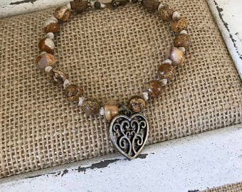 Brown and Tan on knotted hemp.  Has unique wood crosses and bronze scroll heart charm.  8 1/2""