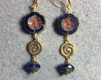 Cobalt blue Czech glass pansy bead dangle earrings adorned with gold swirly connectors and cobalt blue Czech glass Saturn beads.