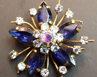 Old vintage brooch has blue rhinestones set forming a flower